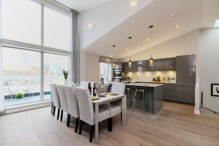 Big double height windows flood this cool grey contemporary open plan kitchen and dining room with natural light. Apartment in an old factory conversion we worked on in London's Southbank. See more of our interior design projects at http://www.janeclayton.co.uk/design-service/