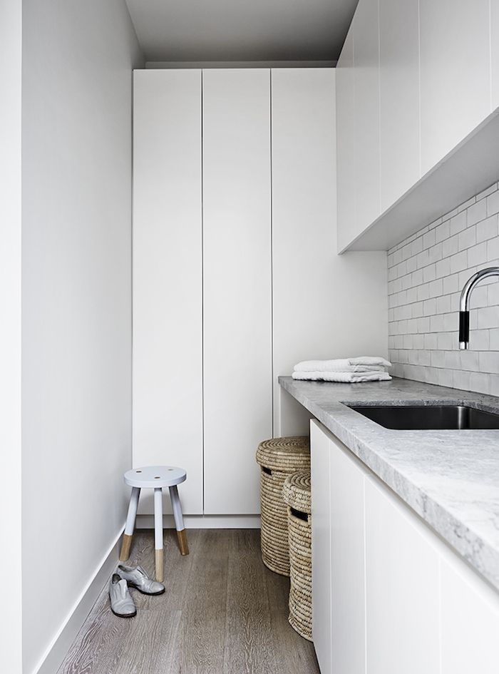 Laundry: white handleless cupboard/cabinet doors, grey marble-look stone benchtop with undermount laundry sink/basin, white handmade subway tile splashback, chrome gooseneck mixer tap with black detail, wicker basket laundry hampers, lilac-dipped wooden stool, timber floorboards
