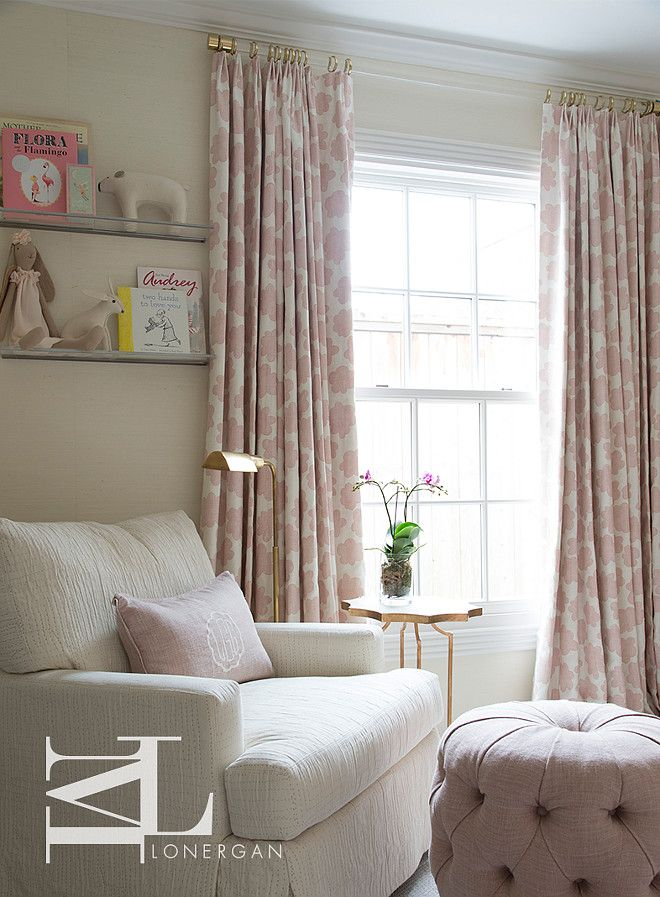 Ivory and pink girl's nursery features corner nursing area boasting an ivory chair adorned with a blush pink monogram pillow facing a pink linen tufted pouf ottoman situated under stacked clear bookshelves beside a marble and brass accent table, Astre Antique Gold Leaf Star Shaped Table, topped with an orchid placed under windows dressed in pink flower curtains. Meg Lonergan.