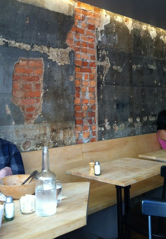 A great touch having the exposed brinck wall peeking through the concrete next to the sleek wood tables and chairs at Back Forty West in New York.: Wall Idea, Concrete Wall, Rustic Wall, Forty West Soho, Textured Walls, Exposed Brick, Distressed Wall, Wall Texture, West Cafe