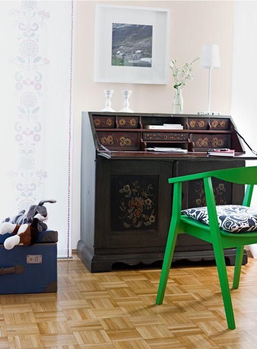 Der antike Sekretär passt sich mit einem grünen Stuhl davor ins freundliche Ambiente ein.