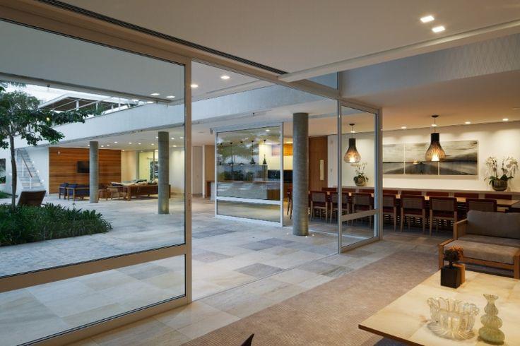 Casa em l tem terra o panor mico e salas abertas for Modelos de piscinas modernas