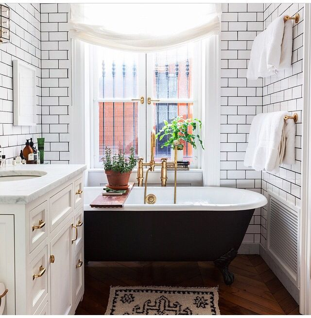 """As a former Manhattan resident, the minute I saw the size of the bathroom and that view I thought, """"That has to be New York."""" And sure enough! Modern subway tile with dark grout, black tub, white vanity, gold hardware."""