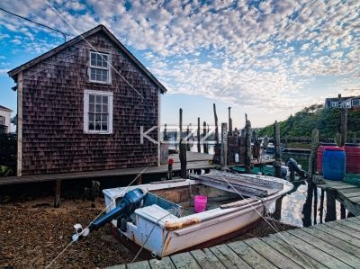 fishing house with boat - A fishing house with a single engine dingy out front.