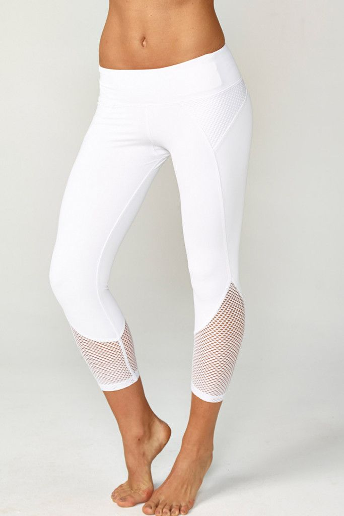 A sleek fashion-forward cropped legging with mesh insets at hips and calves. Comfortable second skin like fabric. Mid-rise, figure contouring waistband.