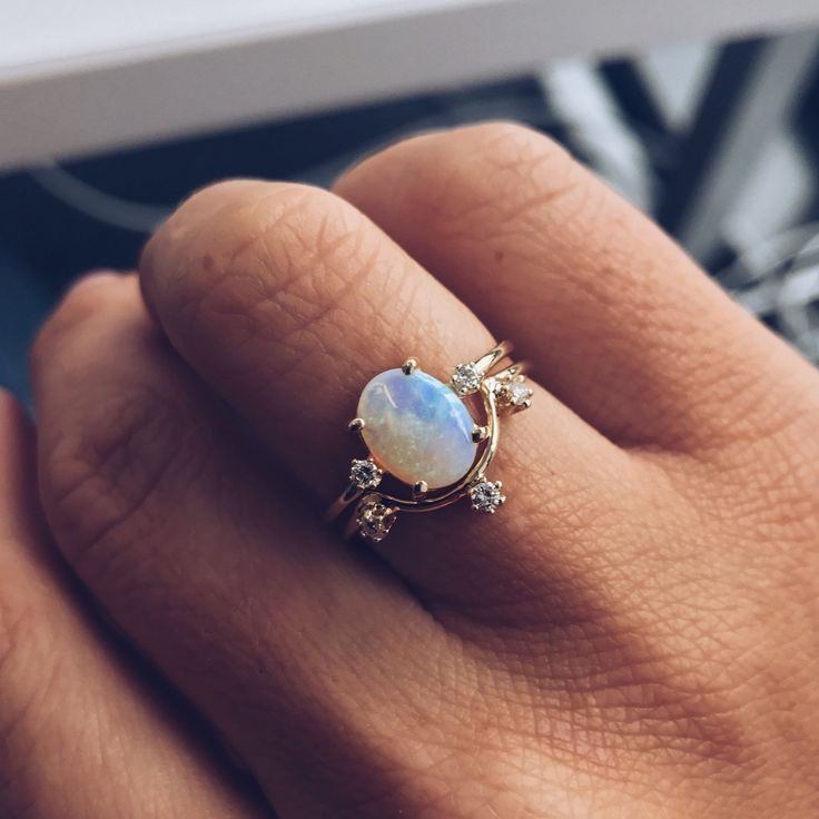 A gorgeous opal ring set with two white diamonds, one on either side. An elegant option for a unique and timeless engagement ring for the bride to be looking for something a little different while sti