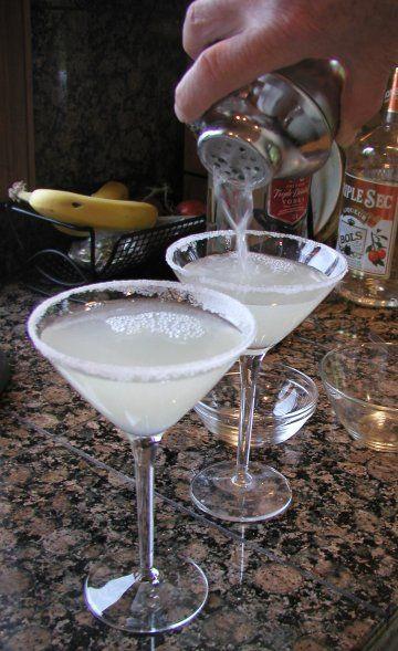 Lemon Drop Martini 1 1/2 ounces vodka (use a good-quality vodka) 1/2 ounce orange liqueur (Triple Sec, Grand Marnier, Cointreau, etc.) 1 teaspoon superfine sugar or to taste* 3/4 ounce freshly-squeezed lemon juice Ice cubes Superfine sugar for dipping Twisted peel of lemon