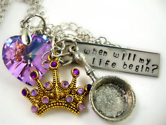 This necklace is inspired by the character Rapunzel from Disneys animated movie Tangled.    A antique silver colored chain with a brass colored lobster clasp, a brilliant purple vitrail colored swarovski crystal heart pendant (to symbolize Rapunzels colors), a rectangular antique silver colored metal stamp with when will my life begin? hand stamped into the pendant, a gold colored metal tiara charm with swarovski rhinestones in shades of purple (to symbolize Rapunzels crown) and a silver…