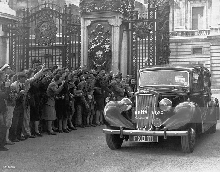 Supporters cheer as newly-elected British Prime Minister Clement Attlee (1883 - 1967) leaves Buckingham Palace after submitting a list of members of the new Labour government to King George VI, 28th July 1945.