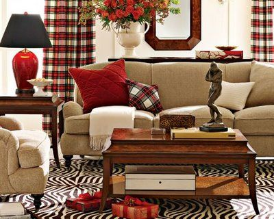 Living room with red accents. Plaid curtains - bold choice. I will never understand putting statuary on the coffee table.