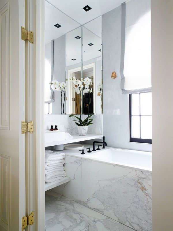 A deep bath with a striking, deep-veined Calacatta marble surround, contrasted with jet-black faucet and fittings by Watermark | archdigest.com