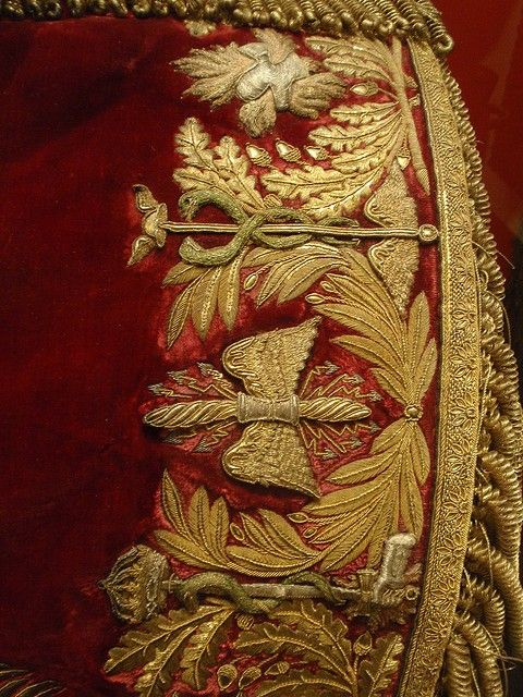 ornamentedbeing:    Elegant gold embroidery on red velvet - part of French officer's uniform    Hand-embroidered, ca. 1800. The details are breathtaking. It's also amazing that this and so many other uniforms survived.    I am ridiculously interested in the caduceus but I can't find anything about why it would be on the uniform or what the other symbols stand for.
