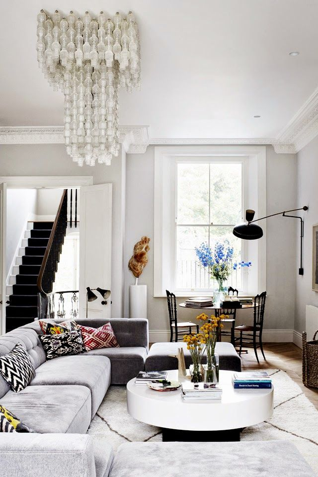 classic architecture with modern furniture and a statement chandelier in this living room by suzy hoodless | via coco+kelley