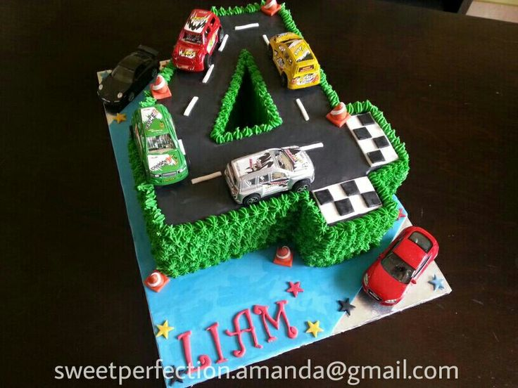 Number 4 shaped cake. Racing track cars theme. Buttercream piped grass, fondant race track & details including mini orange traffic cones.  Toy cars supplied by client.
