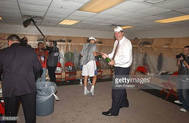 Detroit Shock Head Coach Bill Laimbeer holds a bottle of champagne in the locker room following