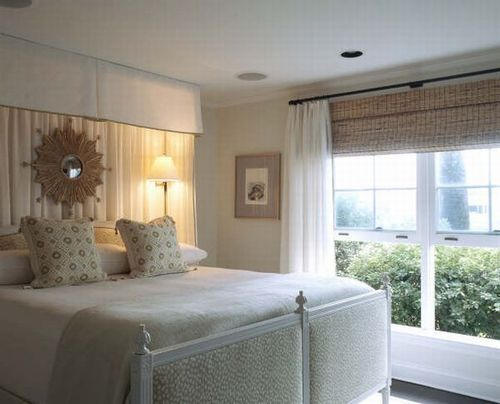 In this bedroom with eight foot ceilings, they hung bamboo blinds above the windows and hung the curtains high. They made a canopy of unlined gauze and hung it all the way up, as well.
