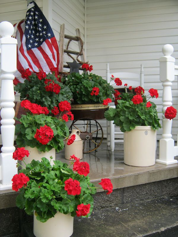 Love the geraniums in the crocks and the flag- Notice planters all the same color