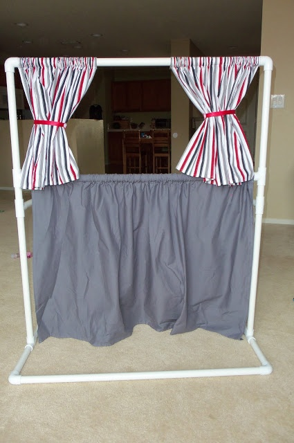 The tutorial is for a kids puppet theater.  I look at this picture & I see a photo shoot backdrop  (more fabric, draped over entire frame & on the floor in the front too).  PVC Pipe section, here I come!
