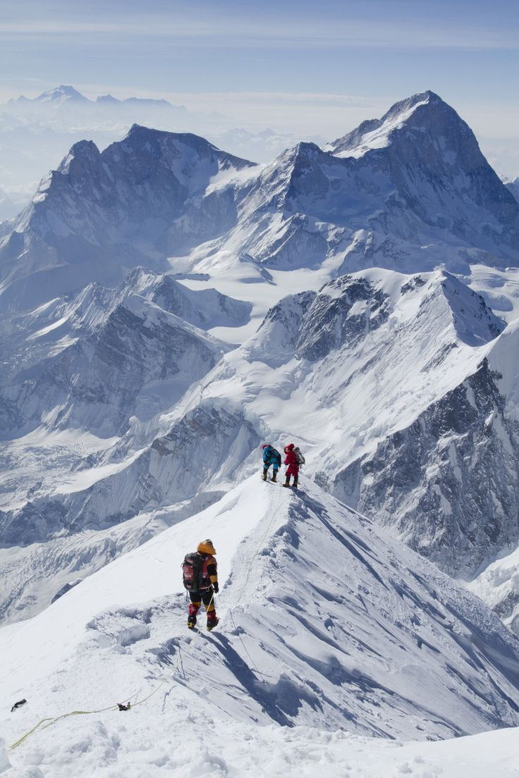 Members of the South Col Five walk along the corniced ridge of the South Summit after their successful climb. Makalu Peak rises in the backg...