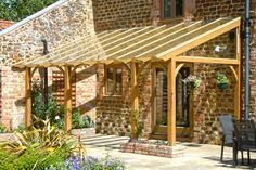 A timber pergola with a glazed roof built as a lean-to on a barn conversion, with small raised brick planters