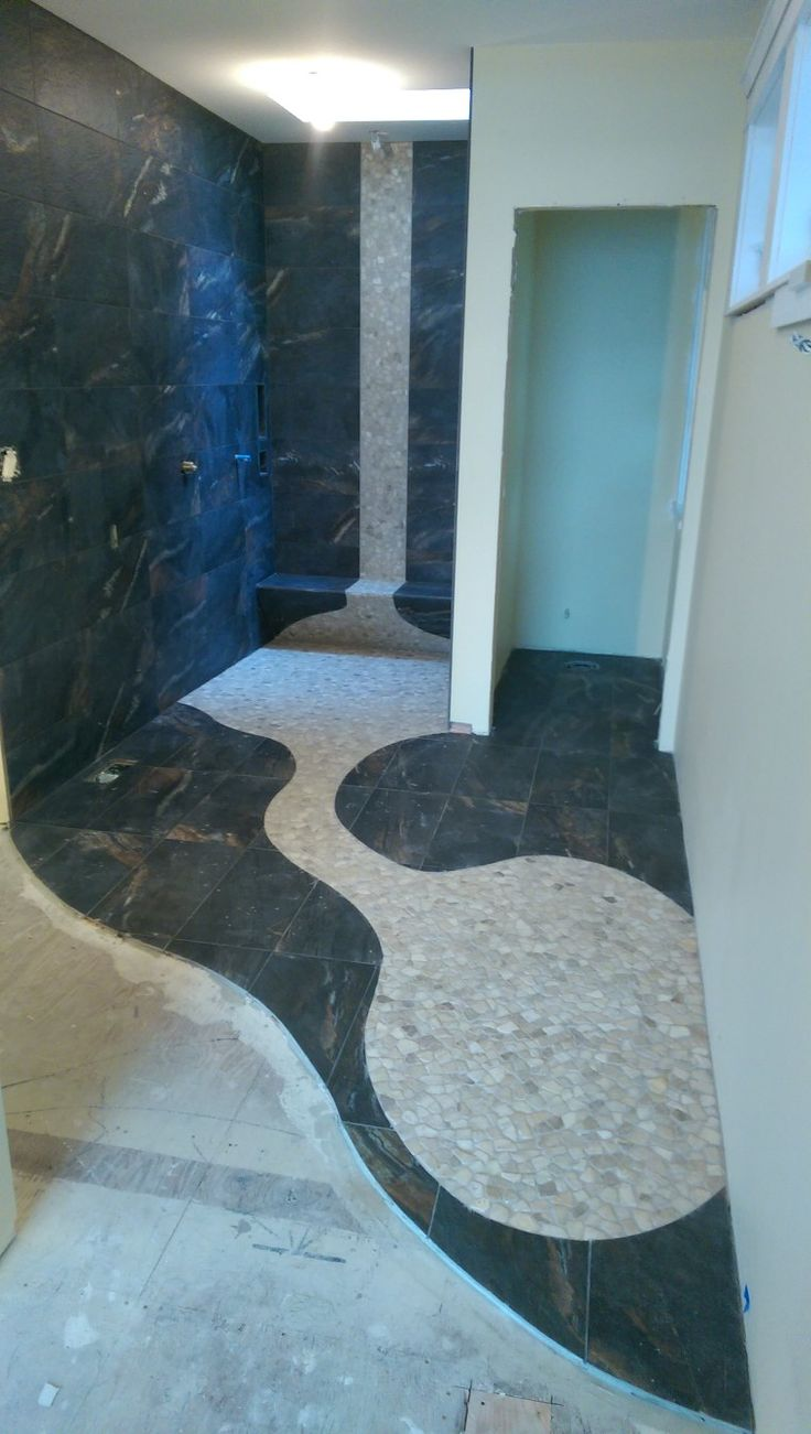 Level entry shower with cut pebble floor and linear drain