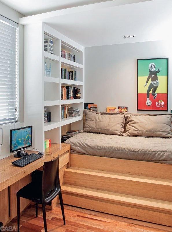 Para aproveitar bem o espaço a cama foi para o canto e usa um dos nichos da estante como mesinha lateral