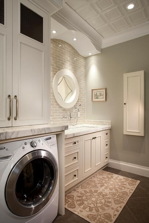 White and gray laundry room features white cabinets paired with thick gray and white marble countertop and a gray brick tile backsplash.