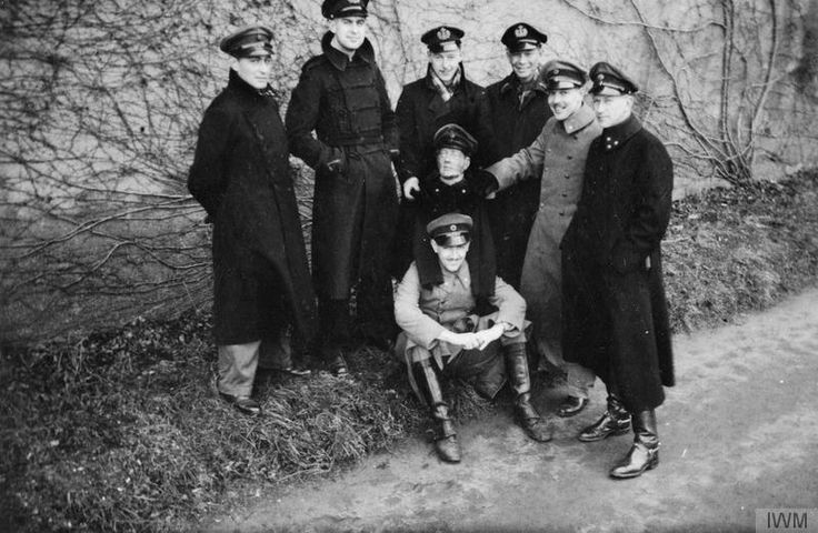 Group of Dutch Navy officers and 'Moritz', one of the two dummy heads of POWs made to mislead German guards during daily roll calls. Oflag IVC, Colditz. Standing from left to right: Lieutenant Gijs van Nimwegen, Lieutenant Diederick van Lynden, Lieutenant Frits Kruimink, Lieutenant Down van der Krapp, Lieutenant Herman Donkers, Major Coen Giebel. Sitting with 'Moritz' on his shoulders is Lieutenant Leo de Hartog. 'Moritz' and 'Max' (second dummy) were made of plaster by a fellow Polish POW…
