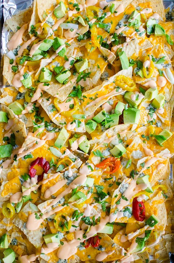 Enjoy all the flavours of Buffalo chicken in this nacho recipe for spicy Buffalo nachos with tons of cheddar and blue cheese, hot peppers and a Buffalo sour cream.   livinglou.com
