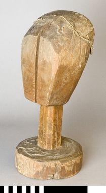 """""""Mösstock av furu. Skulpterat huvud med rakt fäste och rund sockel. Överdelen har lager på lager med klistrad linnelärft och paper."""" ca 1800-1850 DigitaltMuseum - Mösstock"""