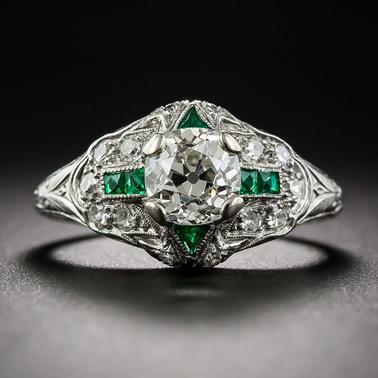 1.10 Carat Diamond Art Deco Engagement Ring with Emerald Calibre. Authentic, original Art Deco engagement rings with high-quality calibre emeralds are highly coveted and exceptionally scarce, and this one is a rare and ravishing beauty. The ring features a gorgeous old mine-cut diamond with a very slight cushion shape outline, weighing 1.10 carats...