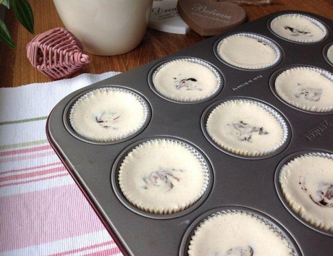 Tvarohový cheesecake s povidly a skořicí, krok 3: Směs rozdělte rovnoměrně do 12 košíčků. Do každého dortíku pak přidejte lžičku povidel. Pomocí párátka můžete povidla lehce promíchat v tvarohu nebo nechat jen tak.