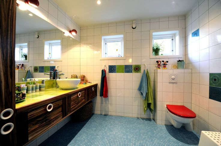Custom Design: Some of the tiles in the bathroom are designed by Anita themselves, and the knobs on the drawers artist has even turned porcelain.  Notice the red toilet seat.