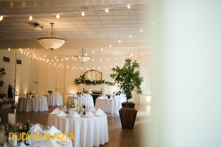 the historic reception hall is ready and waiting for this florida bride. orange trees in varnished wood planters, market lights strung across the dance floor and mantles dressed with lush magnolia, citrus and lemon leaf await the guests .