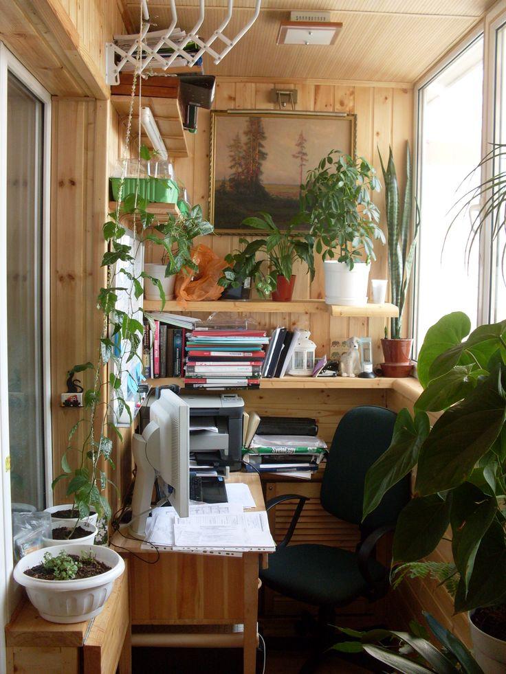 Рабочее место на балконе: полки для документов и книг. принтер, стол с ящиками, кресло, картина, подсветка картины, освещение и цветы.