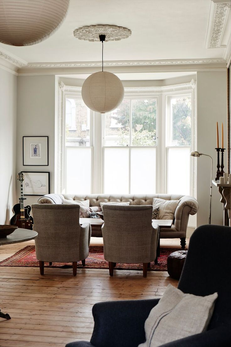 A Refined Terrace House in London by Cassandra Ellis: Remodelista/The walls of the front room are painted French Grey Pale by Little Greene. She maximizes the light without compromising privacy by using an opaque window film on the lower half of the windows. Midcentury paper Akari Light Pendants by Isamu Noguchi hang from original Victorian rosettes in the ceiling.