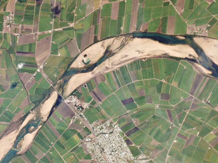 In eastern Queensland, the Burdekin River meanders through a wide floodplain towards its mouth near the Great Barrier Reef. Seasonal flooding deposits large volumes of sand, creating the dramatic, clearly defined floodplain visible in this image. The sugar cane fields surrounding the river are irrigated year-round with water drawn from an extensive underground aquifer system. Image by Planet Labs.