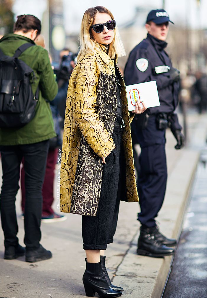 A snake print Stella McCartney coat is worn with a leather jacket, cuffed trousers, ankle boots and black sunglasses