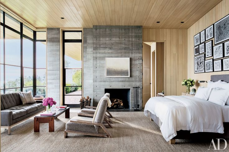 In the master suite of a Malibu home decorated by Denise Kuriger, a Matthew Brandt photograph is mounted over the fireplace, and ink drawings by Van Hanos are displayed above the bed. The sofa and bed, conceived by Kuriger and architectural designer Scott Mitchell, are upholstered in de Le Cuona fabrics; the low table is from JF Chen.
