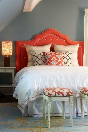 Like the padded coral-orange headboard against the warm gray wall & the separate end stools.