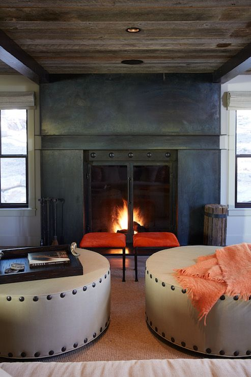 Cozy living room with steel framed fireplace surround with glass doors framed by a pair of black framed windows either side. A pair of iron based orange stools stand in front of the fireplace behind a pair of round linen ottomans with oversize nailhead trim over hardwood floors layered with a sisal rug.