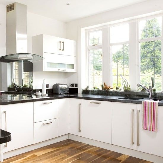 This pristine kitchen makes the most of natural light with crisp white walls and understated units. The granite-topped worksurfaces are chic and practical. Colour contrast is brought in with candy pink accessories.
