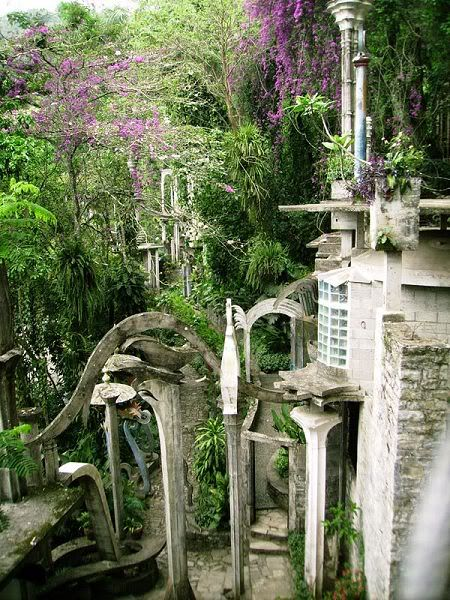 """Las Pozas (""""the Pools"""") is a sculpture garden built by Edward James more than 2,000 feet (610 m) above sea level, in a tropical rain forest in the mountains of Mexico. It includes more than 80 acres (320,000 m2) of natural waterfalls and pools interlaced with towering Surrealist sculptures in concrete."""