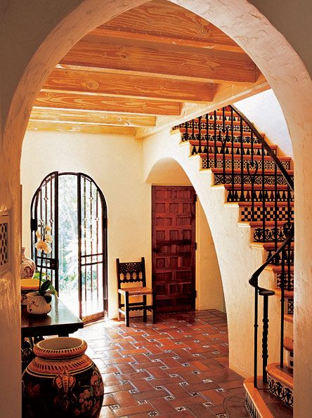 Clay tiles in a lattice-weave patern with hand-decorated accent tiles ground a Spanish Colonial Revival house.