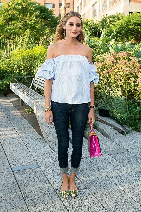 Olivia Palermo wears an off-the-shoulder blouse, cuffed jeans, floral ballet flats, statement earrings, and a pink bag: