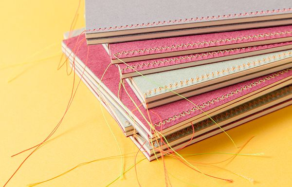 Three Mrs. Stitches notebooks that show their luminous threads on the covers with a sewing technique called Herringbone stitch.