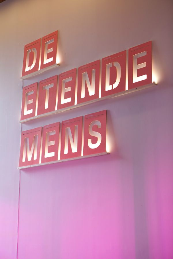 De Etende Mens' the exhibition graphics by Raw Color. The title of the show is highlighted from behind by fluorescent tubes.