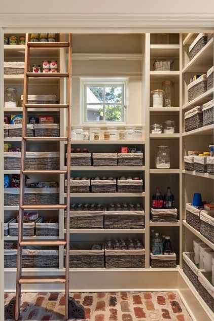 Tall pantry with ladder maximizes space by going vertical. A library ladder ensures that the shelves are reachable, while cute linen-lined baskets and a rustic brick floor reinforce the kitchen's farmhouse feel.