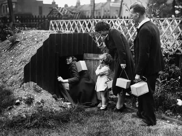 A family goes into an Anderson air raid shelter in their garden, 1939. Each person carries a gas mask in a little box.