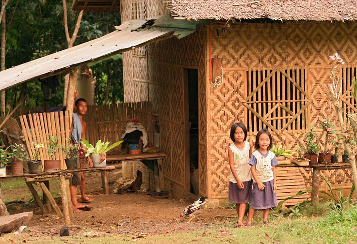 A Man And Two Young Girls Standing Outside Their Home A